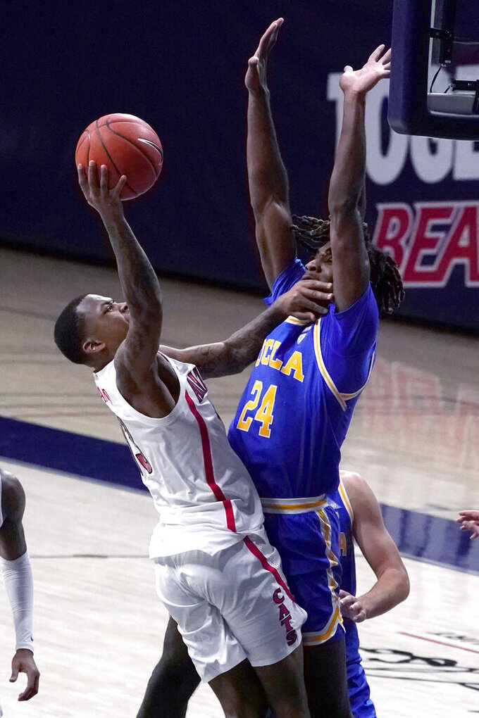 Arizona guard James Akinjo drives on UCLA forward Jalen Hill (24) during the first half of an NCAA college basketball game Saturday, Jan. 9, 2021, in Tucson, Ariz. (AP Photo/Rick Scuteri)