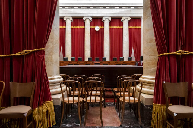 FILE - In this June 24, 2019, file photo, the empty courtroom is seen at the U.S. Supreme Court in Washington. The lack of transparency at the Supreme Court begins with the heavy red drapes that frame the courtroom on all sides. The court replaced the drapes this summer, but it would not reveal the name of the company that did the work. The Supreme Court's role in a bitterly divided Washington and nation may be more important than ever, yet basic details about how the court operates remain obscured. (AP Photo/J. Scott Applewhite, File)