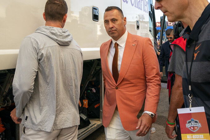 Texas head coach Steve Sarkisian walks from the bus into the Cotton Bowl stadium before an NCAA college football game against Oklahoma, Saturday, Oct. 9, 2021, in Dallas. (AP Photo/Jeffrey McWhorter)