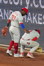 Philadelphia Phillies center fielder Odubel Herrera (37) checks on right fielder Bryce Harper after Harper injured himself while attempting to catch a double off the right field wall hit by Pittsburgh Pirates' Ke'Bryan Hayes during the fourth inning of a baseball game in Pittsburgh, Friday, July 30, 2021. Harper remained in the game. (AP Photo/Gene J. Puskar)