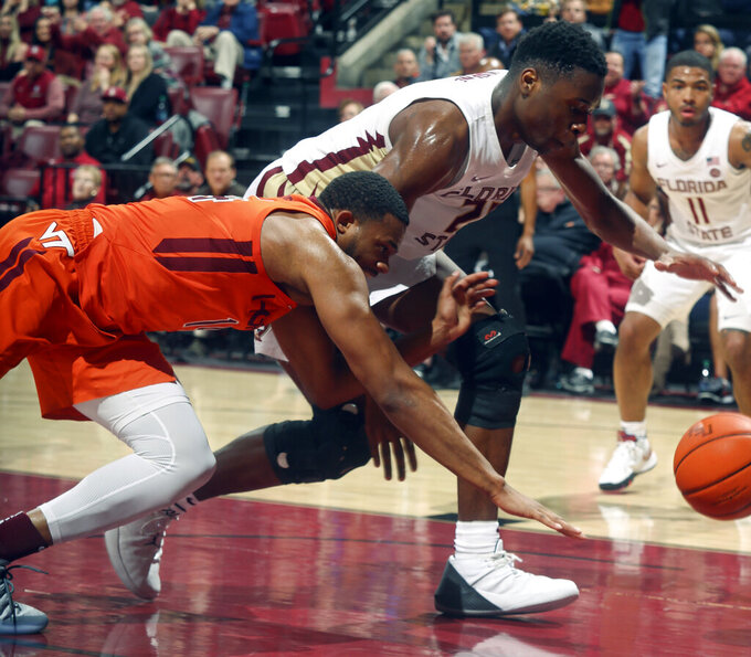 Virginia Tech forward P.J. Horne (14) loses a ball out of bounds as Florida State forward Mfiondu Kabengele (25) gives chase in the second half of an NCAA college basketball game in Tallahassee, Fla., Tuesday, March 5, 2019. Florida State won 73-64 in overtime. (AP Photo/Phil Sears)