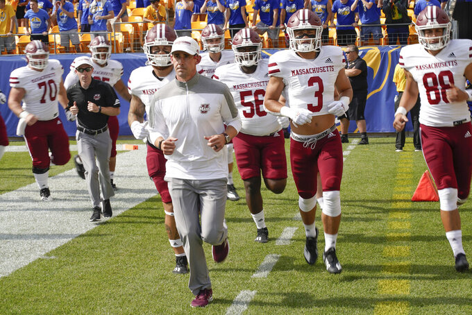 Massachusetts head coach Walt Bell leads his team onto the field to play against Pittsburgh in an NCAA college football game, Saturday, Sept. 4, 2021, in Pittsburgh. (AP Photo/Keith Srakocic)