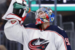 Columbus Blue Jackets goaltender Elvis Merzlikins, of Latvia, sprays himself during a timeout in the second period of the team's NHL hockey game against the St. Louis Blues on Friday, Nov. 1, 2019, in St. Louis. (AP Photo/Jeff Roberson)