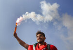 A student protester holds a smoke flare during a protest against the government in front of the education ministry in Beirut, Lebanon, Friday, Nov. 8, 2019. Lebanese protesters are rallying outside state institutions and ministries to keep up the pressure on officials to form a new government to deal with the country's economic crisis. (AP Photo/Hussein Malla)