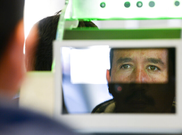 FILE - In this Dec. 10, 2015, file photo, a pedestrian crossing from Mexico into the United States at the Otay Mesa Port of Entry has his facial features and eyes scanned at a biometric kiosk in San Diego. The Trump administration says it's planning to expand the collection of biometric information as part of immigration enforcement. (AP Photo/Denis Poroy, File)