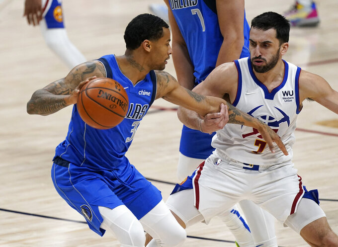 Dallas Mavericks guard Trey Burke, left, is defended by Denver Nuggets guard Facundo Campazzo during the first half of an NBA basketball game Saturday, March 13, 2021, in Denver. (AP Photo/David Zalubowski)