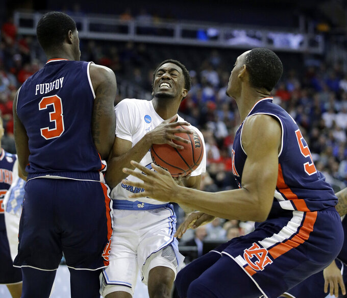 North Carolina's Brandon Robinson, center, heads to the basket past Auburn's Danjel Purifoy (3) and Austin Wiley, right, during the first half of a men's NCAA tournament college basketball Midwest Regional semifinal game Friday, March 29, 2019, in Kansas City, Mo. (AP Photo/Charlie Riedel)