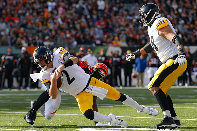Pittsburgh Steelers quarterback Mason Rudolph (2) grounds the ball under pressure from Cincinnati Bengals defensive end Carl Lawson (58) during the first half an NFL football game, Sunday, Nov. 24, 2019, in Cincinnati. (AP Photo/Gary Landers)