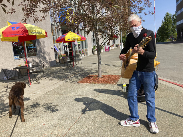 Street musician Cal Austermuhl performs on a street in downtown Anchorage, Alaska Wednesday, July 1, 2020, the same day Alaska residents began receiving their share of the state's oil wealth. Austermuhl says his $992 share was already spent on bills. (AP Photo/Mark Thiessen)