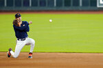 Houston Astros shortstop Carlos Correa throws to second baseman Jose Altuve during a baseball practice at Minute Maid Park, Sunday, July 5, 2020, in Houston. (AP Photo/David J. Phillip)