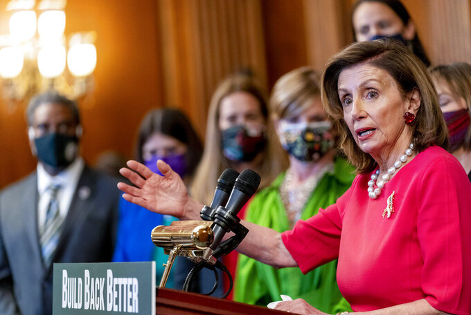 """House Speaker Nancy Pelosi of Calif., accompanied by other House Democrats and climate activists, pauses while speaking about their """"Build Back Better on Climate"""" plan on Capitol Hill in Washington, Tuesday, Sept. 28, 2021. (AP Photo/Andrew Harnik)"""