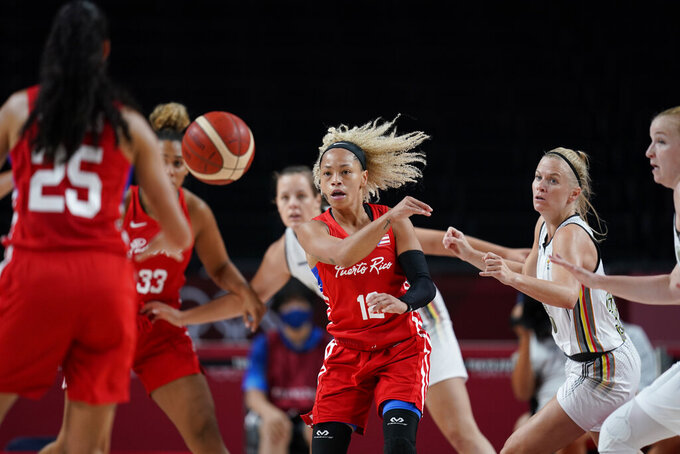 Puerto Rico's Dayshalee Salaman (12), center, passes to a teammate during women's basketball preliminary round game against Belgium at the 2020 Summer Olympics, Friday, July 30, 2021, in Saitama, Japan. (AP Photo/Charlie Neibergall)