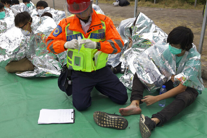 A medical worker attends to an injured youth at a casualty evacuation point near Hong Kong Polytechnic University in Hong Kong, Tuesday, Nov. 19, 2019. About 100 anti-government protesters remained holed up at a Hong Kong university Tuesday as a police siege of the campus entered its third day. (AP Photo/Ng Han Guan)