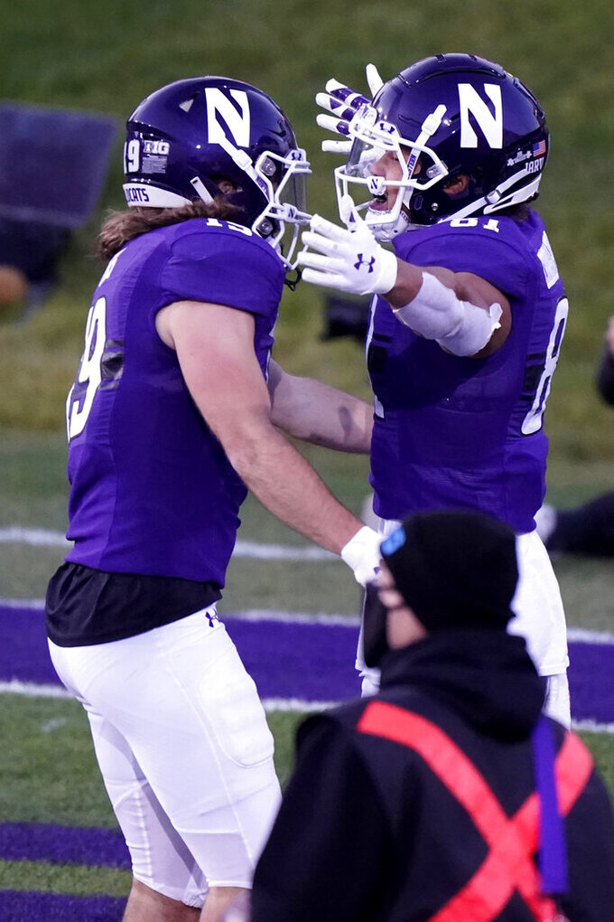 Northwestern wide receiver Ramaud Chiaokhiao-Bowman, right, celebrates with wide receiver Riley Lees after catching a touchdown pass during the first half of an NCAA college football game against Wisconsin in Evanston, Ill., Saturday, Nov. 21, 2020. (AP Photo/Nam Y. Huh)