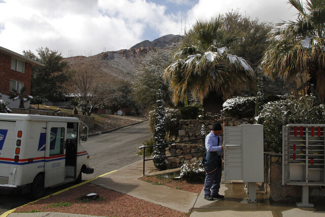 Snow can be seen on palm trees while mail carrier Pablo Salinas delivers letters on Wednesday, Feb. 5, 2020, in El Paso, Texas. Salinas said his commute took an extra hour due to road closures following four inches of snow falling overnight. (AP Photo/Cedar Attanasio)