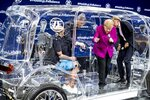 German Chancellor Angela Merkel climbs out of a transparent car with security devices during her visit to the IAA Auto Show in Frankfurt, Germany, Thursday, Sept. 12, 2019. (AP Photo/Michael Probst)