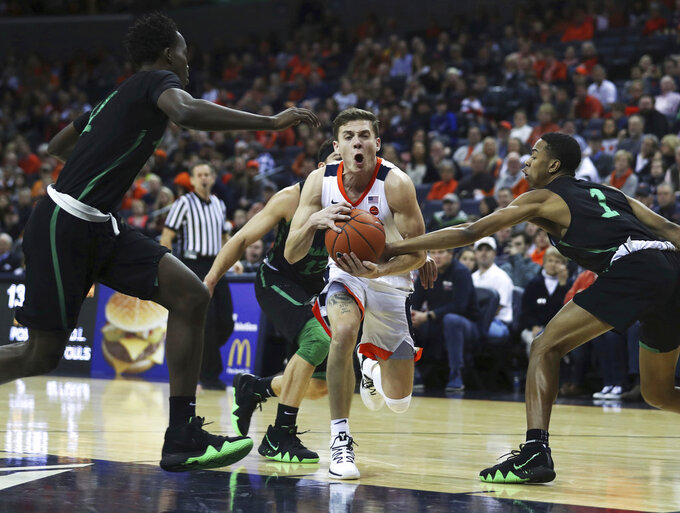 Virginia's guard Kyle Guy (5) is caught between three Marshall defenders in the first half of an NCAA college basketball game on Monday, Dec. 31, 2018, in Charlottesville, Va. (AP Photo/Zack Wajsgras)