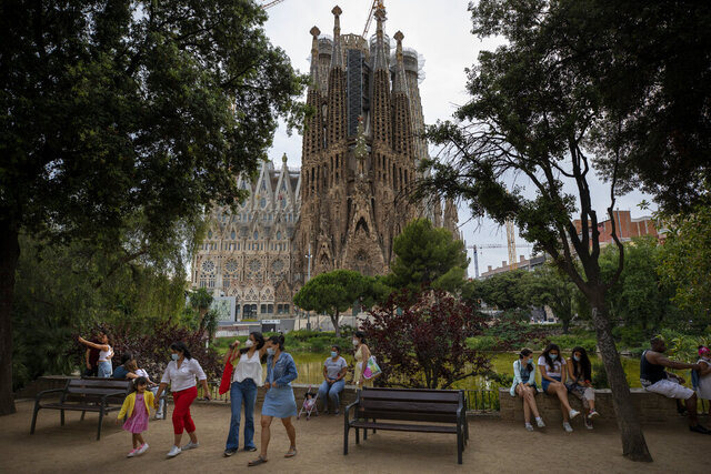 In this Sunday, May 31, 2020 photo, local visitors enjoy a park next to the Antoni Gaudí's La Sagrada Familia Basilica in Barcelona. Spain's national statistics office said that it received zero international tourists in April after the nation had closed its borders at the height of its coronavirus outbreak. (AP Photo/Emilio Morenatti)