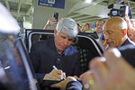 Former Illinois Gov. Rod Blagojevich signs a baseball after he arrived at O'Hare International Airport in Chicago, following his release from Colorado prison on Tuesday, Feb. 18, 2020. Blagojevich had walked out of prison Tuesday after President Donald Trump cut short the 14-year prison sentence handed to the former Illinois governor for political corruption. (Tim Boyle/Chicago Sun-Times via AP)