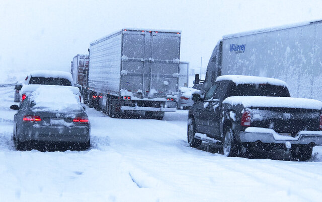 This photo provided by Johnny Lim shows a snow covered northbound I-15 in the Cajon Pass between the San Bernardino Mountains and the San Gabriel Mountains in Southern California on Thursday, Dec. 26, 2019. Lim, of Corona, said he's been stuck in his vehicle for about five hours on his way to Las Vegas. A powerful winter storm brought a deluge of rain and snow to Southern California, triggering tornado warnings and bringing post-Christmas travel to a halt on major routes. (Johnny Lim via AP)