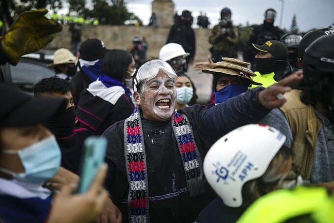 A demonstrator shouts at police during an anti-government protest in Bogota, Colombia, Wednesday, June 9, 2021. Ongoing protests have been triggered by proposed tax increases on public services, fuel, wages and pensions. (AP Photo/Ivan Valencia)