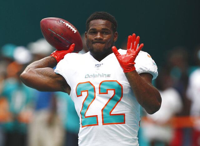 FILE - In this Sept. 8, 2019, file photo, Miami Dolphins running back Mark Walton (22) warms up before an NFL football game against the Baltimore Ravens, in Miami Gardens, Fla. The Dolphins have released troubled running back Mark Walton, saying he had been involved in an unspecified police matter. Tuesday's, Nov. 19, 2019,  announcement came as the second-year player served a four-game suspension for violating NFL conduct and substance abuse policies. (AP Photo/Brynn Anderson, File)