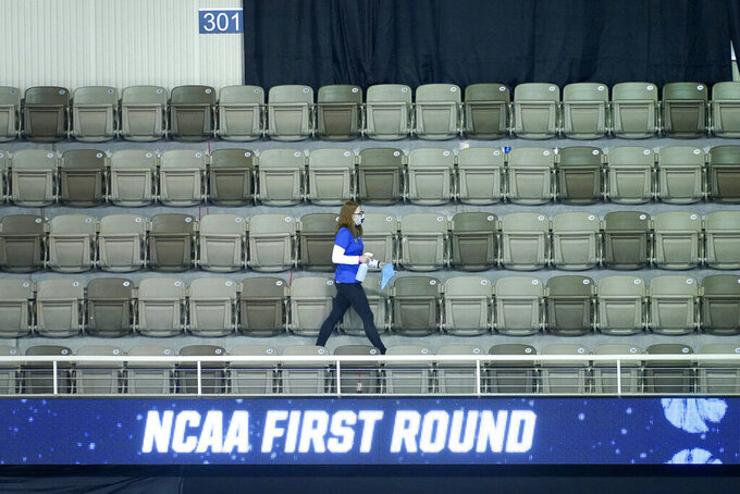 A worker at the Indiana Farmers Coliseum in Indianapolis, sanitize seats between first round NCAA college basketball tournament games Friday, March 19, 2021. (AP Photo/Charles Rex Arbogast)