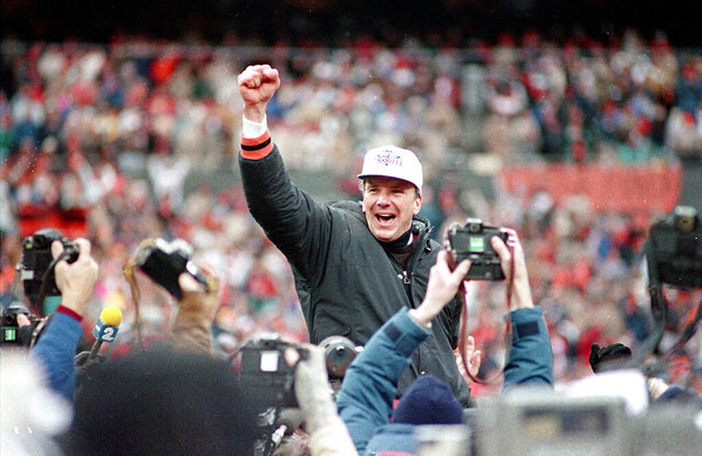 FILE - In this Jan. 9, 1989 file photo, Cincinnati Bengals coach Sam Wyche clenches his fist as he is carried from the field on the shoulders of his players after their 21-10 victory over the Buffalo Bills for the AFC Championship game in Cincinnati , Ohio. Sam Wyche, who pushed the boundaries as an offensive innovator with the Cincinnati Bengals and challenged the NFL's protocols along the way, has died, Thursday, Jan. 2, 2020. He was 74.  (AP Photo/Rob Burns, File)