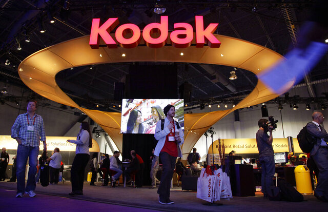 FILE - In this Jan. 11, 2012 file photo, buyers and industry affiliates pass by the Kodak exhibit at the 2012 International CES trade show in Las Vegas.  An independent legal review has determined that there were several flaws in how Eastman Kodak gave stock option grants to its CEO prior to the once formidable photography company being awarded a loan from the Trump administration.  (AP Photo/Julie Jacobson, File)