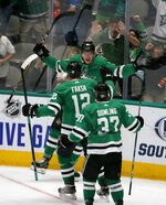 Dallas Stars right wing Joel L'Esperance (38) celebrates with center Radek Faksa (12) and center Justin Dowling (37) after his goal during the second period of the team's NHL hockey game against the Calgary Flames in Dallas, Thursday, Oct. 10, 2019. (AP Photo/Michael Ainsworth)