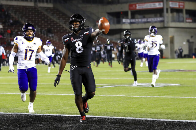 Cincinnati wide receiver Michael Young Jr. holds the ball up as he scores a touchdown during the first half of the team's NCAA college football game against East Carolina, Friday, Nov. 13, 2020, in Cincinnati. (AP Photo/Aaron Doster)