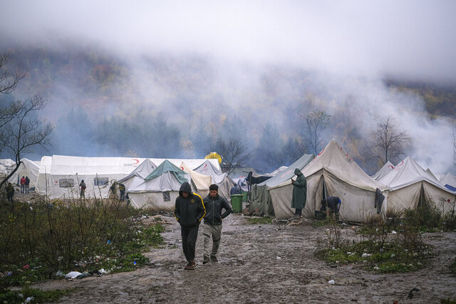 In this Wednesday, Nov. 20, 2019, photograph, migrants walk at the Vucjak refugee camp outside Bihac, northwestern Bosnia. Hundreds of refugees and migrants remain stuck in northwest Bosnia in a makeshift camp described by numerous international organizations as dangerous and inhuman, where desperate men, including many who have made several unsuccessful attempts to cross into neighboring European Union member Croatia, sleep in a tent camp located on a former landfill, not far from a mine field left over from Bosnia's 1992-95 war.(AP Photo/Kemal Softic)