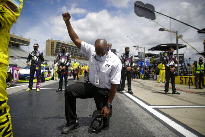 A NASCAR official kneels during the national anthem before a NASCAR Cup Series auto race at Atlanta Motor Speedway, Sunday, June 7, 2020, in Hampton, Ga. NASCAR paused before Sunday's Cup race at Atlanta Motor Speedway to acknowledge the country's social unrest. (AP Photo/Brynn Anderson)