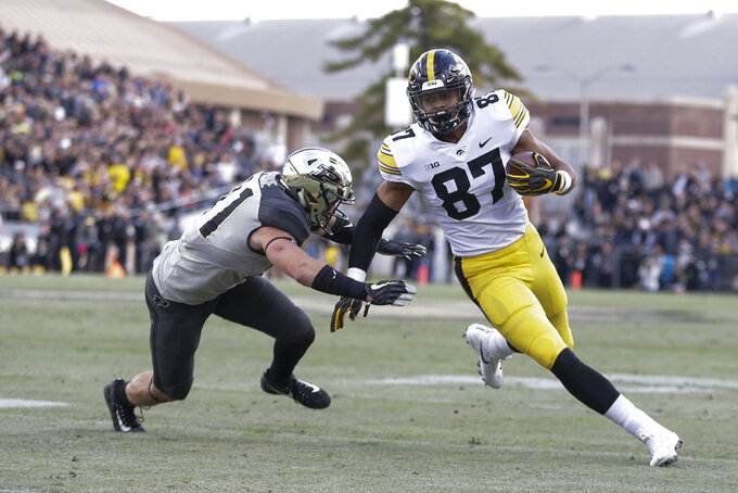 Iowa tight end Noah Fant (87) runs from the defense of Purdue safety Jacob Thieneman (41) in the first half of an NCAA college football game in West Lafayette, Ind., Saturday, Nov. 3, 2018. (AP Photo/AJ Mast)
