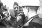 This photo provided by Alabama Department of Archives and History, from January 1966 shows Simuel Schutz Jr. speaking to a police officer during a protest following the shooting of a black man by a white man in Tuskegee, Ala. Schutz, who was active in the civil rights movement, says he was part of a group that later tried to topple a Confederate monument at the center of the mostly black city. (James Peppler/Alabama Department of Archives and History via AP)