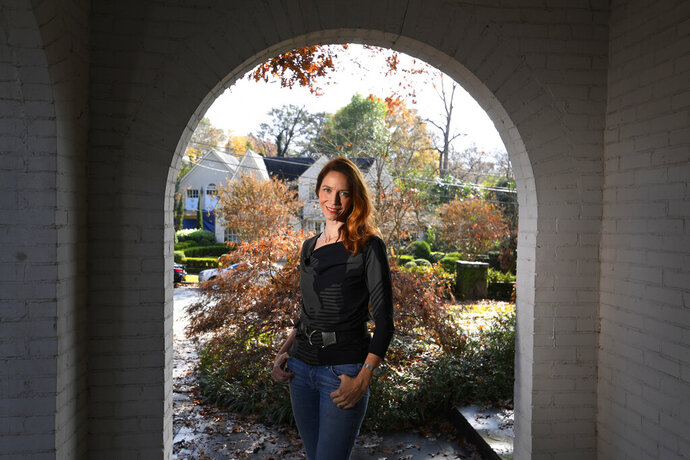 In this Nov. 27, 2019, photo, Georgia Tech professor Kim Cobb poses for a photo at her home in Atlanta. Some climate scientists and activists, including Cobb, are limiting their flying, their consumption of meat and their overall carbon footprints to avoid adding to the global warming they study. (AP Photo/John Amis)