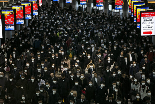 FILE - In this Tuesday, March 3, 2020, file photo, a large crowd wearing masks commutes through Shinagawa Station in Tokyo. World War II references are now heard daily, not because another momentous 75th anniversary, Victory in Europe Day approaches in May but because of the coronavirus. (AP Photo/Jae C. Hong, File)