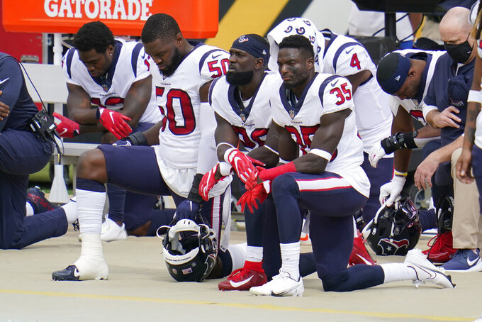 Some of the Houston Texans kneel as others stand for the playing of the National Anthem before an NFL football game against the Pittsburgh Steelers, Sunday, Sept. 27, 2020, in Pittsburgh. (AP Photo/Gene J. Puskar)