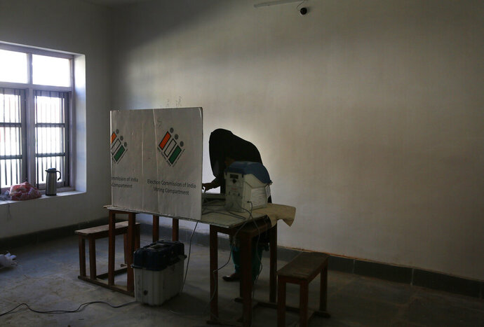 A Kashmir burqa clad woman casts her vote inside a polling station during the third phase of India's general elections, at Verinag, south of Srinagar, Indian controlled Kashmir, Tuesday, April 23, 2019. Kashmiri separatist leaders who challenge India's sovereignty over the disputed region have called for a boycott of the vote during the third phase of Indian general election. (AP Photo/Mukhtar Khan)