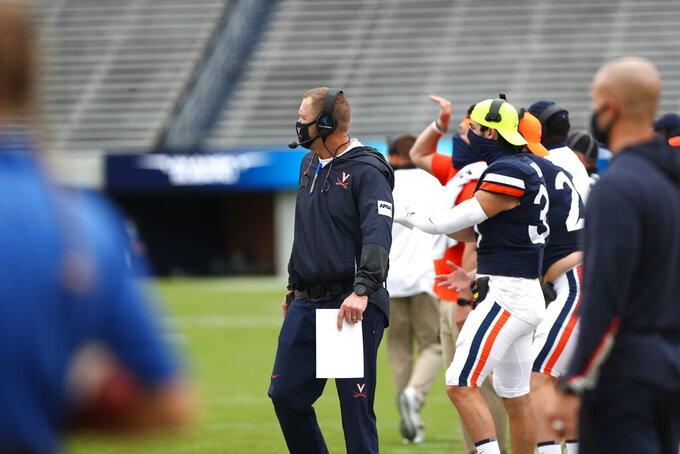 Virginia head coach Bronco Mendenhall, center, watches a play during an NCAA college football gamea gainst Duke, Saturday, Sept. 26, 2020, in Charlottesville, Va. (Erin Edgerton/The Daily Progress via AP)