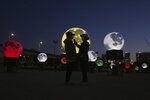 Women stand next to glowing full moon installations at a park in Seoul, South Korea, Friday, Sept. 18, 2020. The artificial full moons have been installed by a local officials to increase morale during the COVID-19 outbreak and to celebrate the upcoming Chuseok holiday, the Korean version of Thanksgiving Day. (AP Photo/Ahn Young-joon)