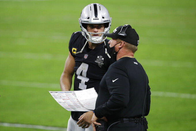Las Vegas Raiders quarterback Derek Carr (4) speaks with head coach Jon Gruden during the second half of an NFL football game Miami Dolphins, Saturday, Dec. 26, 2020, in Las Vegas. (AP Photo/Steve Marcus)
