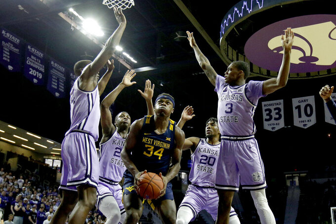West Virginia's Oscar Tshiebwe (34) looks for a shot under pressure from Kansas State's Makol Mawien (14) and DaJuan Gordon (3) during the first half of an NCAA college basketball game Saturday, Jan. 18, 2020, in Lawrence, Kan. (AP Photo/Charlie Riedel)