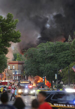 Smoke rises as firefighters work the scene of an explosion in downtown Sun Prairie, Wis., Tuesday, July 10, 2018. The explosion rocked the downtown area of Sun Prairie, a suburb of Madison, after a contractor struck a natural gas main Monday, sending an unknown number of people to hospitals, authorities said. (Amber Arnold/Wisconsin State Journal via AP)