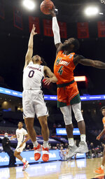 Miami guard Elijah Olaniyi (4) blocks the shot of Virginia guard Kihei Clark (0) during an NCAA college basketball game Monday in Charlottesville, Va. (Andrew Shurtleff/The Daily Progress via AP, Pool)
