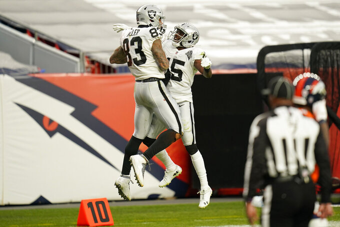 Las Vegas Raiders tight end Darren Waller (83) and wide receiver Nelson Agholor (15) celebrate after Waller scored a touchdown against the Denver Broncos during the first half of an NFL football game, Sunday, Jan. 3, 2021, in Denver. (AP Photo/Jack Dempsey)
