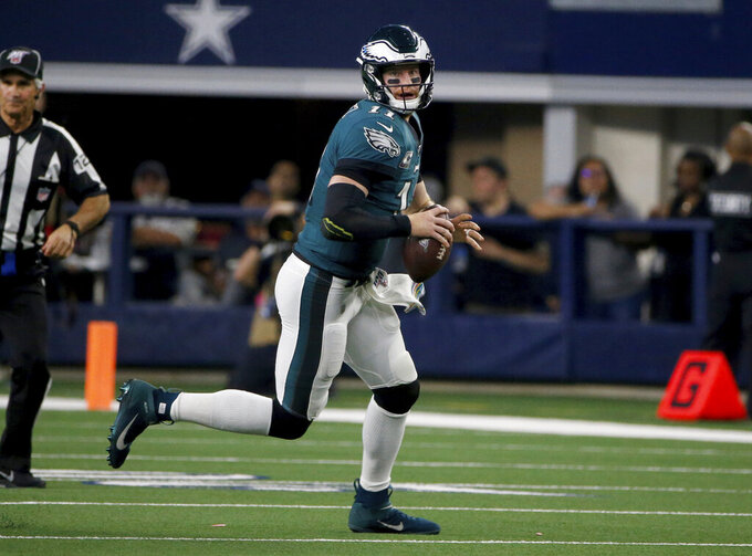 Philadelphia Eagles quarterback Carson Wentz (11) scrambles out of the pocket in the second half of an NFL football game against the Dallas Cowboys in Arlington, Texas, Sunday, Oct. 20, 2019. (AP Photo/Michael Ainsworth)
