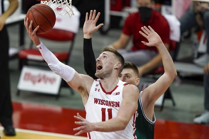 Wisconsin's Micah Potter shoots past Wisconsin-Green Bay's Cem Kirciman during the second half of an NCAA college basketball game Tuesday, Dec. 1, 2020, in Madison, Wis. (AP Photo/Morry Gash)