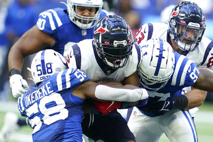 Houston Texans' Mark Ingram (2) is tackled by Indianapolis Colts' Bobby Okereke (58) and Al-Quadin Muhammad (97) during the second half of an NFL football game, Sunday, Oct. 17, 2021, in Indianapolis. (AP Photo/Michael Conroy)