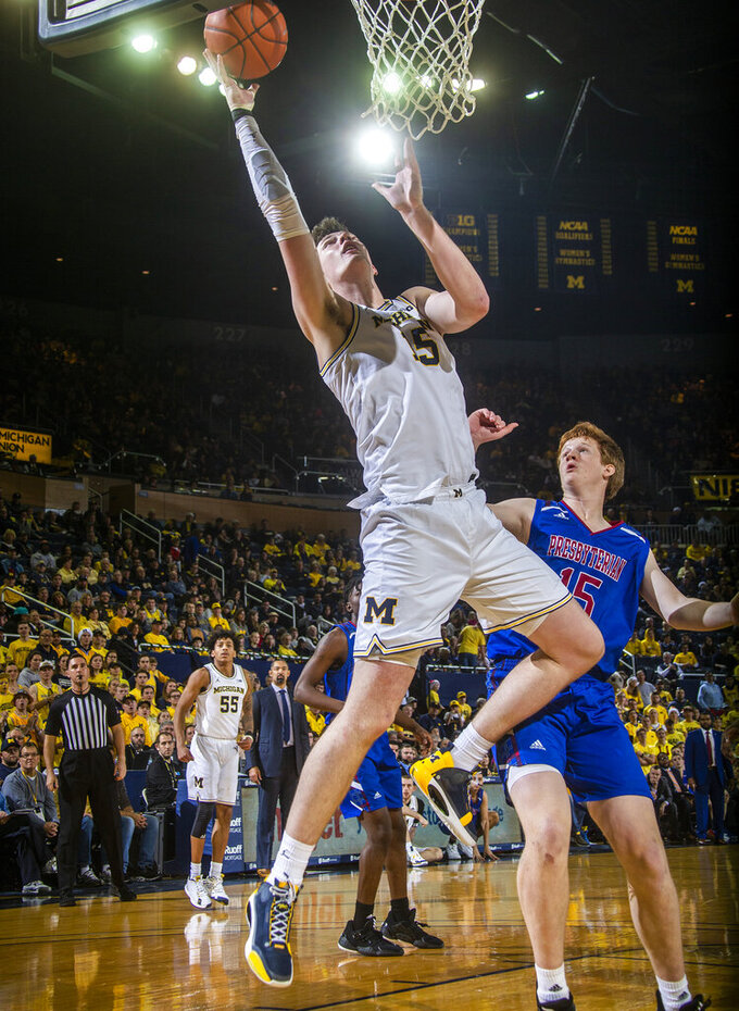 Michigan center Jon Teske, front, makes a basket ahead of Presbyterian forward Owen McCormack, right, in the second half of an NCAA college basketball game at Crisler Center in Ann Arbor, Mich., Saturday, Dec. 21, 2019. Michigan won 86-44. (AP Photo/Tony Ding)